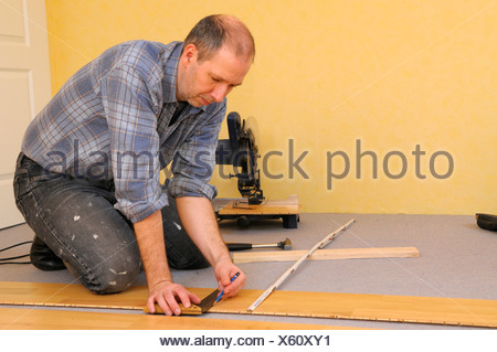Man laying parquet flooring - Stock Photo