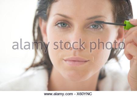 Young woman applying mascara, portrait, close-up - Stock Photo