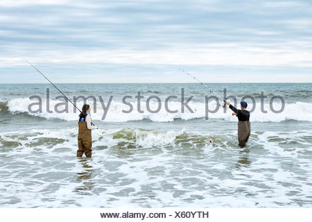 Young couple in waders, casting off sea fishing rods in sea - Stock Photo