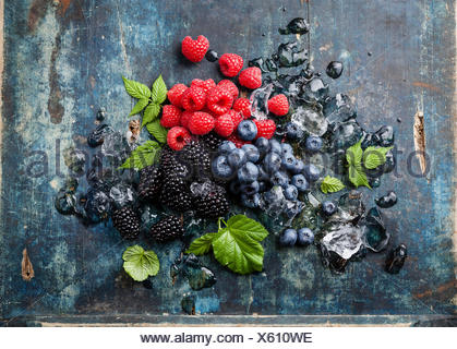 Mix of fresh berries with ice on blue wooden background - Stock Photo
