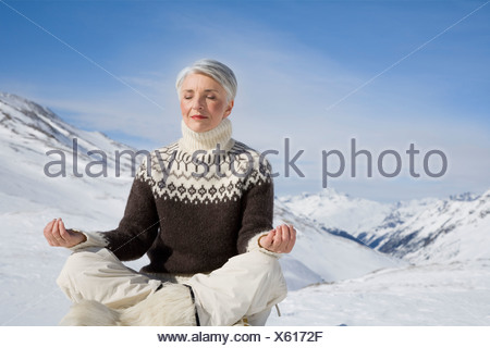 Mature woman doing yoga in mountains on winter day - Stock Photo