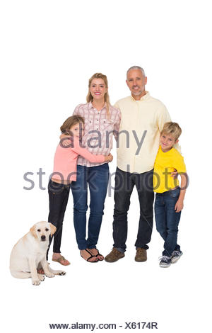 Happy family smiling at camera with pet dog - Stock Photo