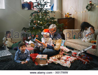 Father and four children opening christmas gifts in sitting room - Stock Photo