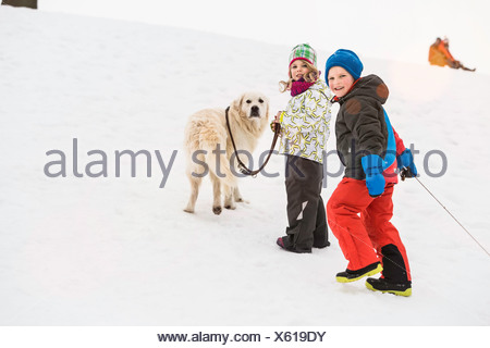 Boy and girl walking dog in snow - Stock Photo