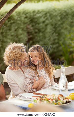 Mother and daughter sitting at table outdoors - Stock Photo