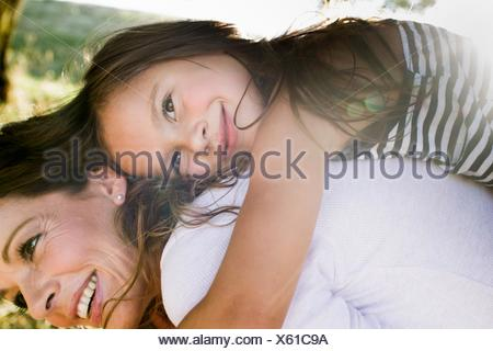 Mature woman giving daughter piggy back in park - Stock Photo
