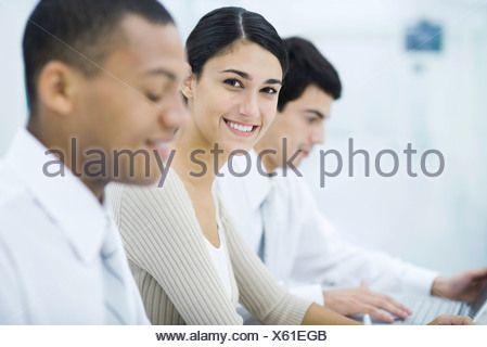 Young professional woman sitting between two male colleagues, smiling at camera - Stock Photo