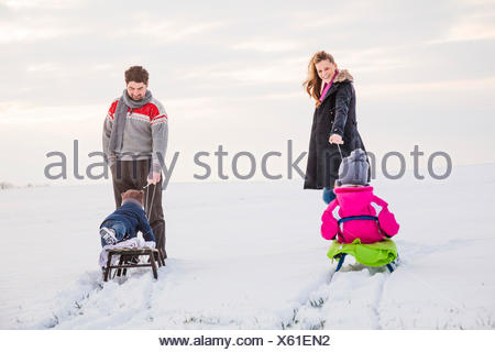 Happy family sledging in snow - Stock Photo