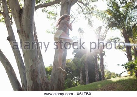 Young woman having fun on rope swing - Stock Photo