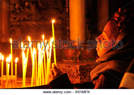 Young believer with tears in her eyes lighting a candle at the grave of Christ in the Church of the Holy Sepulchre, Jerusalem,  - Stock Photo