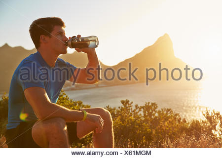 Young man drinking after jogging - Stock Photo