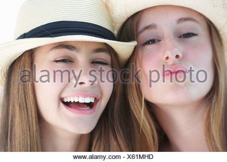 Portrait of two teenage girls wearing hats - Stock Photo