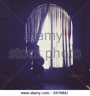Side View Of Pregnant Woman Looking Out Window At Home - Stock Photo