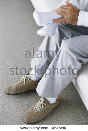 Child sitting on man's lap, cropped view - Stock Photo