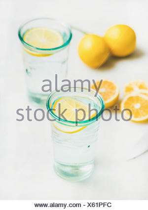 Morning detox lemon water in glasses served with fresh lemons over light grey marble background, selective focus. Clean eating, weight loss, healthy,  - Stock Photo