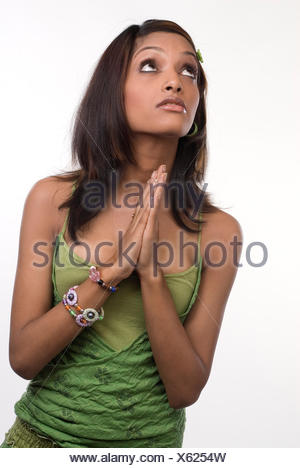 Woman folding her hands in prayer - Stock Photo
