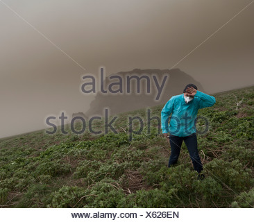 Woman wipes the ash from her eyes from Grimsvotn Volcanic Eruption in the Vatnajokull Glacier, Iceland - Stock Photo
