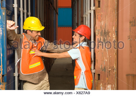 Two dock workers having a playful fight between rows of cargo containers - Stock Photo