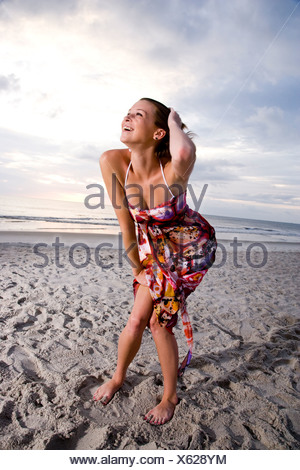 Happy young woman in colorful sundress standing on beach laughing - Stock Photo