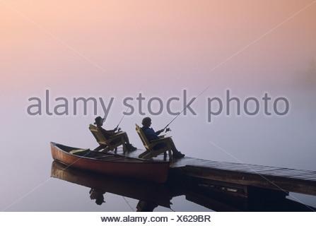 Couple Fishing off Dock, Winnipeg River, Pinawa, Manitoba - Stock Photo