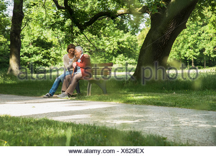 Senior woman sitting on park bench with granddaughter - Stock Photo