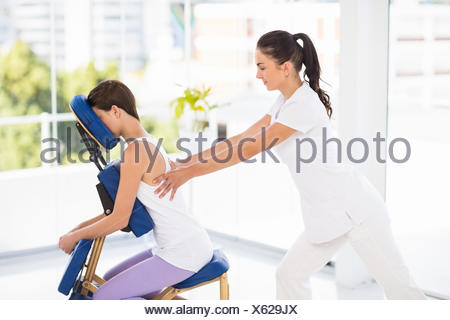 Woman being massaged on chair by masseuse - Stock Photo