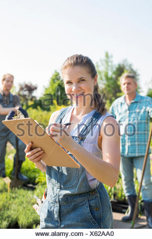 Portrait of beautiful supervisor holding clipboard with gardeners standing in background at plant nursery - Stock Photo