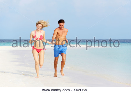 Romantic Couple Running On Beautiful Tropical Beach - Stock Photo