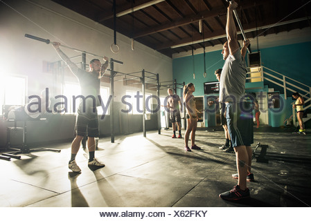 Man and personal trainer lifting barbell in gym - Stock Photo