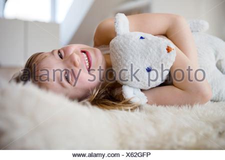 Girl lying on furry bed cuddling teddy bear - Stock Photo
