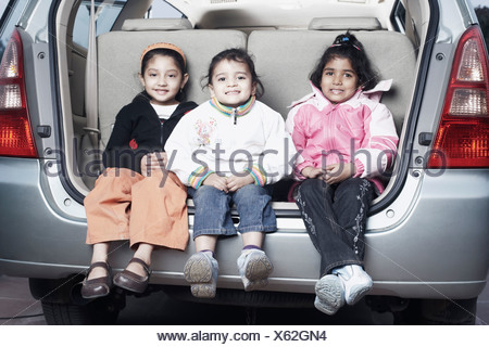 Portrait of three sisters sitting in the back of a car - Stock Photo