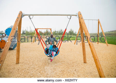 Father pushing daughters in swing net at playground - Stock Photo
