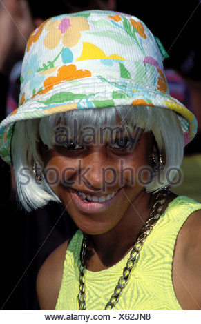 Young Afro Caribbean woman wearing a blond wig colourful hat at Southwark Show London - Stock Photo