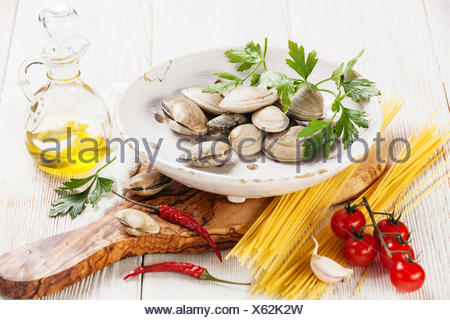 Ingredients for cooking spaghetti vongole Shells vongole, raw spaghetti, parsley leaves, cherry tomatoes - Stock Photo