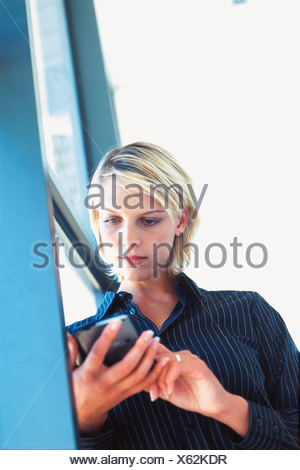Businesswoman using personal organiser - Stock Photo