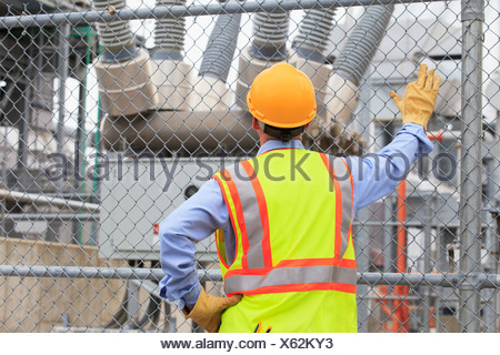 Electrical engineer examining transformers inside of an electric power plant - Stock Photo