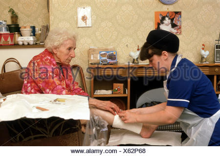 home help carers district nurse on a home visit tending to elderly woman with leg ulcers - Stock Photo