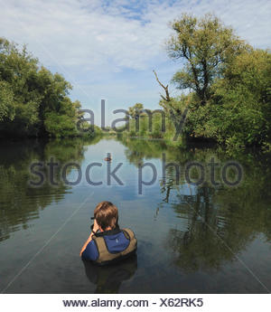 Wildlife photographer, Bertie Gregory, photographing a great crested grebe, Podiceps cristatus, while submerged in a river - Stock Photo