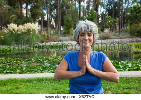Mature woman meditating in park - Stock Photo