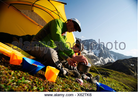 Hikers prepare a morning meal at camp on the Williwaw Lakes Trail in Chugach State Park near Anchorage,Southcentral Alaska - Stock Photo