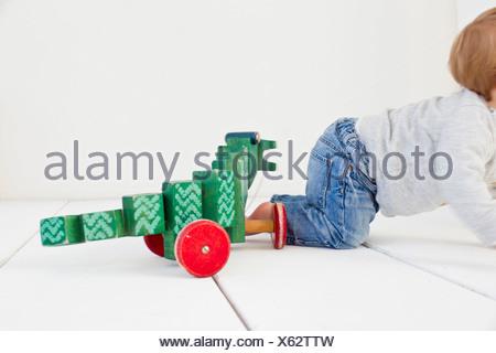 Studio shot of baby girl and wheeled toy - Stock Photo
