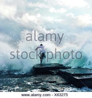 Waves Crashing At Rocks And Man - Stock Photo