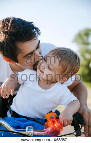Father kissing his little son on bicycle tour - Stock Photo