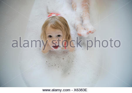 Overhead portrait wide-eyed girl laying bubble bath - Stock Photo
