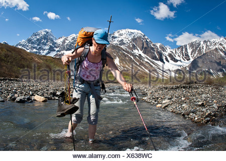 Female backpacker crossing the Babel River below South Buttress on the western flanks of the Revelation Mountains, Alaska - Stock Photo