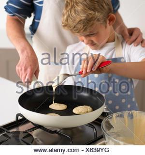 Pouring pancake batter in a frying pan - Stock Photo