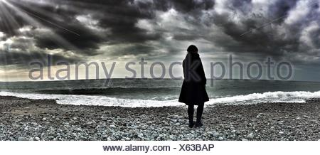 Panoramic Shot Of Person Standing On Beach Against Cloudy Sky - Stock Photo