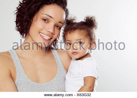 Portrait of young woman holding baby daughter in studio - Stock Photo