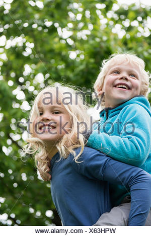 Young blonde girl carrying brother piggyback - Stock Photo