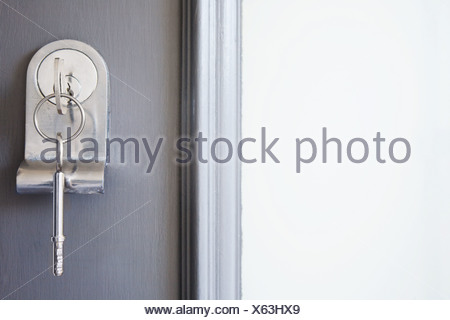 Close up of key in a front door - Stock Photo